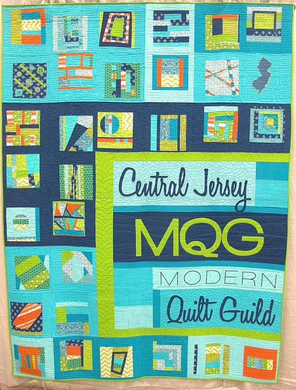 Central New Jersey MQG Banner by members of the Central jersey MQG. Phillipsburg, New Jersey. Pieced by Neva Asinari, Janet Bergman, Amy Blanchard, Helen Branch, Robin Buscemi, Christina Di Marco, Susan Flick, Andy Foster, Elaine Hagaman, Tatiana Kennedy, Jessica Levitt, Sandy Mahaney, Teddi Munslow, Lori Saporito, Linda Schulz, Rachel Singh, Jessica Skultety. Quilted by Jessica Levitt. 3rd place, Group or Bee Quilts, QuiltCon 2015.
